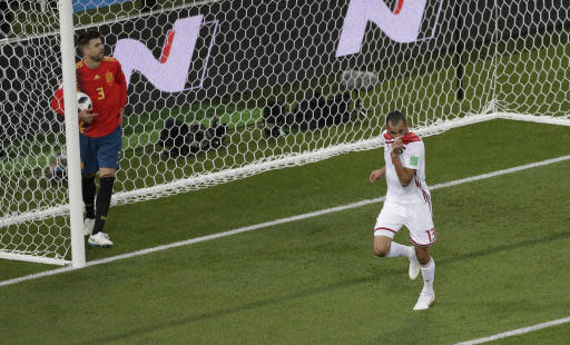 Morocco's Khalid Boutaib, right, celebrates after scoring his side opening goal as Spain's Gerard Pique, left, holds the ball during the group B match between Spain and Morocco at the 2018 soccer World Cup in the Kaliningrad Stadium in Kaliningrad, Russia, Monday, June 25, 2018. (AP Photo/Michael Sohn)