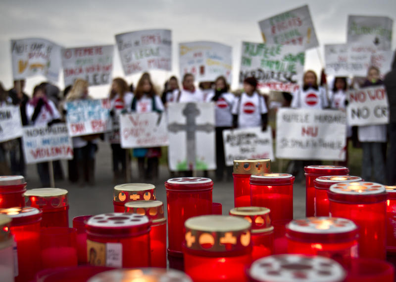 In this Friday, Nov. 25, 2011 file photo, candles for the victims of domestic violence burn during a protest in Bucharest, Romania. About a third of women worldwide have been physically or sexually assaulted by a former or current partner, according to the first major review of violence against women. In a series of papers released on Thursday June 20, 2013 by the World Health Organization and others, experts estimated nearly 40 percent of women killed worldwide were slain by an intimate partner and that being assaulted by a partner was the most common kind of violence experienced by women. (AP Photo/Vadim Ghirda, File)