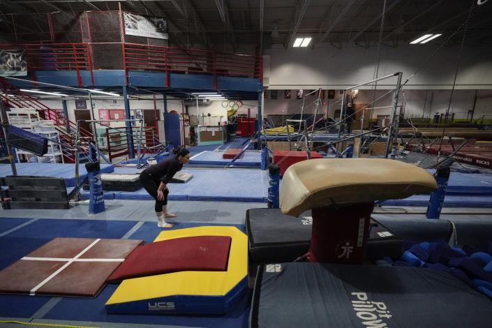 Former gymnastics world champion and Olympic silver medalist Chellsie Memmel works out Thursday, Feb. 18, 2021, in New Berlin, Wisc. Memmel rediscovered her love for the sport, so much so the married mother of two is making an unlikely comeback. (AP Photo/Morry Gash)