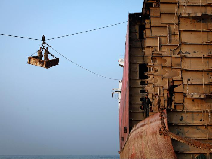Labourers transport supplies to a ship by a makeshift cable carriage to separate it into scrap metal at the Gaddani shipbreaking yard early in the morning, about 60 km (37 miles) from Karachi November 25, 2011.