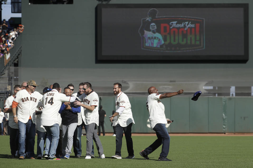Los Angeles Dodgers manager Dave Roberts, in center of group at left, is mobbed by former San Francisco Giants teammates as Barry Bonds, right, throws Roberts' Dodgers hat during a ceremony honoring Giants manager Bruce Bochy after a baseball game between the Giants and the Dodgers in San Francisco, Sunday, Sept. 29, 2019. (AP Photo/Jeff Chiu, Pool)