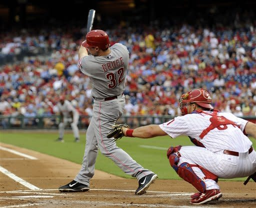 Cincinnati Reds' Jay Bruce (32) watches his ball go deep to right field in front of Philadelphia Phillies' Erik Kratz for a double in the first inning of a baseball game on Monday, Aug. 20, 2012, in Philadelphia. (AP Photo/Michael Perez)