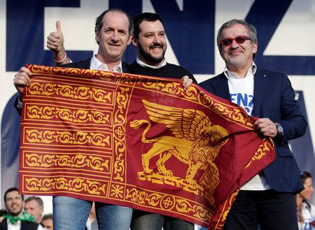 FILE PHOTO: Northern League party leader Matteo Salvini poses with the Lion of Saint Mark flag, with politicians Luca Zaia and Roberto Maroni, during a rally in downtown Rome
