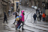 Many people wearing face masks as they move along a shopping street as rain falls in Nottingham, England, Tuesday Oct. 27, 2020. The Nottingham area will move into the Tier 3 highest level of coronavirus restrictions on upcoming Thursday because of a surge in COVID-19 cases. (Joe Giddens/PA via AP)