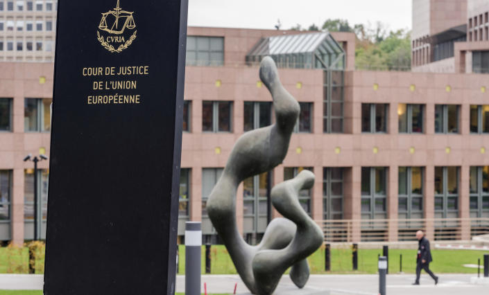 FILE - In this Oct. 5, 2015 file photo, a man walks by the European Court of Justice in Luxembourg. Google is heading to a top European Union court on Monday, Sept. 27, 2021 to appeal a record EU antitrust penalty imposed for stifling competition by abusing the dominance of its Android operating system. (AP Photo/Geert Vanden Wijngaert, File)