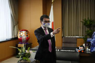 Taro Kono, Japan's minister in charge of a huge vaccination campaign, wearing a face mask gestures after an interview with The Associated Press at his office in Tokyo Wednesday, July 28, 2021. As Olympics host Tokyo saw another record number of coronavirus cases Wednesday, Kono told that the speed of the inoculation campaign, which is averaging about 10 million shots a week after a late start, is less urgent than getting shots to young people, who are blamed for spreading the virus. (AP Photo/Eugene Hoshiko)