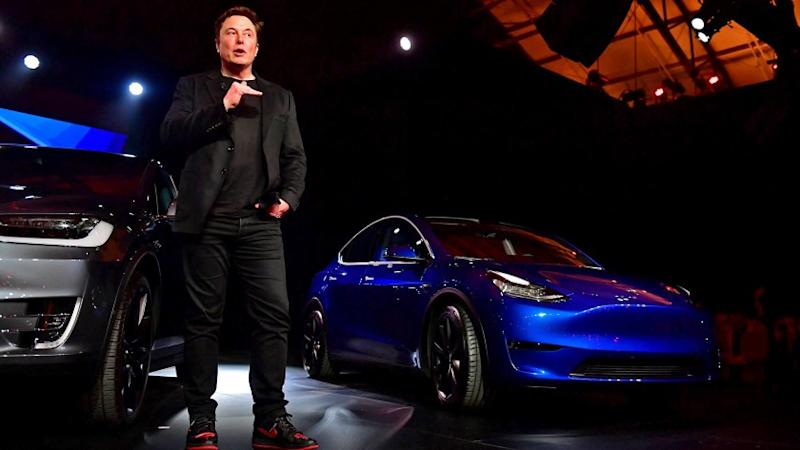 Tesla CEO Elon Musk speaks beside the new Tesla Model Y, right, after introducing it at the Tesla Design Studio in Hawthorne, Calif. on Mar. 14, 2019.