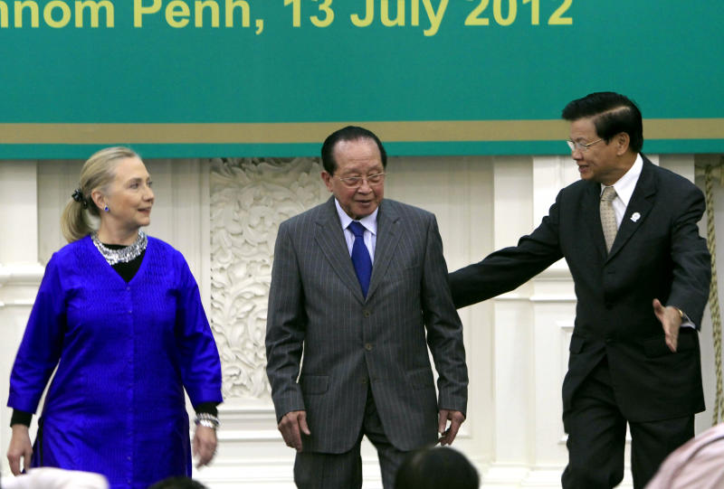 Laos's Foreign Minister Thongloun Sisoulith, right, escorts his Cambodia's counterpart Hor Namhong, center, to his seat as U.S. Secretary of State Hillary Rodham Clinton, left, looks on during the 5th Lower Mekong Initiative (LMI) Foreign Ministers Meeting in Phnom Penh, Cambodia, Friday, July 13, 2012. (AP Photo/Heng Sinith)