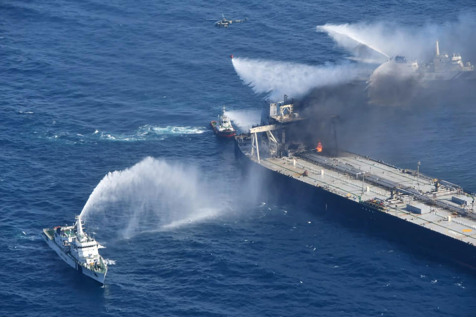 In this photo provided by Sri Lanka Air Force, tug boats and ships battle the fire on MT New Diamond, off the eastern coast of Sri Lanka in the Indian Ocean, Saturday, Sept. 5, 2020. The fire on the large oil tanker off Sri Lanka's coast has been brought under control but is still not extinguished, the navy said Saturday. The tanker, carrying nearly 2 million barrels of crude oil, was drifting about 20 nautical miles (37 kilometers) from Sri Lanka's eastern coast and on Friday evening a tug boat towed it to the deep sea away from land, said navy spokesman Capt. Indika de Silva. (Sri Lanka Air Force via AP)