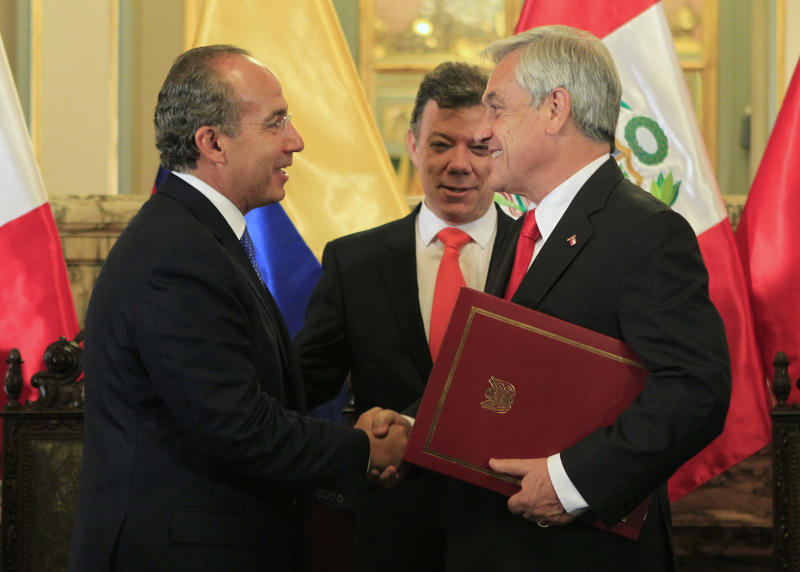 Chile's President Sebastian Pinera, right, shakes hands with Mexico's President Felipe Calderon, left, as Colombia's President Juan Manuel Santos, center, looks on at the government palace in Lima, Peru, Thursday, April 28, 2011. Presidents of Chile, Mexico, and Colombia will meet with Peru's President Alan Garcia to discuss and possibly sign an agreement to establish commercial links with Asian countries of the Pacific region. (AP Photo/Martin Mejia)