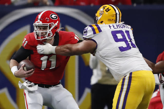 LSU defensive lineman Breiden Fehoko (91) ties up Georgia quarterback Jake Fromm (11) during the second half of the Southeastern Conference championship NCAA college football game, Saturday, Dec. 7, 2019, in Atlanta. (AP Photo/John Bazemore)