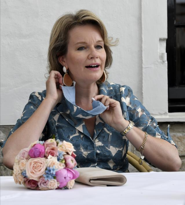 Queen Mathilde, of Belgium, takes off her matching covering as she visits a cafe. (Getty Images)