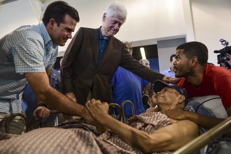 Former President Bill Clinton, top center, and Puerto Rico Governor Ricardo Rossello, left, greet Luis Andrew Torres Carrasquillo, right, and his father, a war veteran, Luis Torres Alemar, laying down, at the William Rivera Betancourt Vocational School which has been turned into an emergency shelter for families affected by the impact of Hurricane Maria, in Canovanas, Puerto Rico, Monday, Nov. 20, 2017. (AP Photo/Carlos Giusti)
