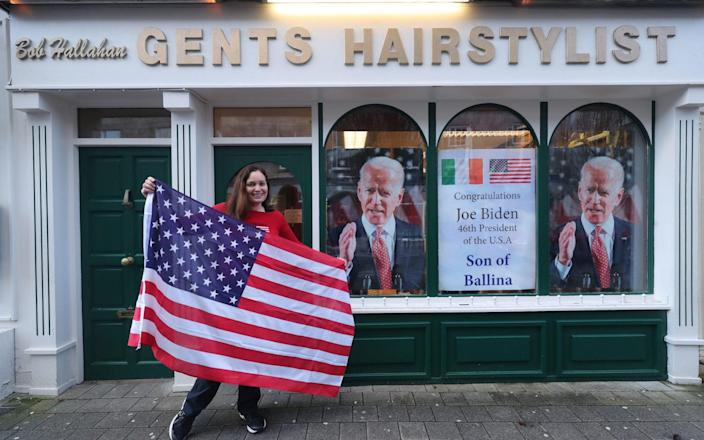 Catherine Hallahan prepares to hang an American flag inside her family's hairdressers in Ballina, Co Mayo to mark Mr. Biden's inauguration - Niall Carson/PA