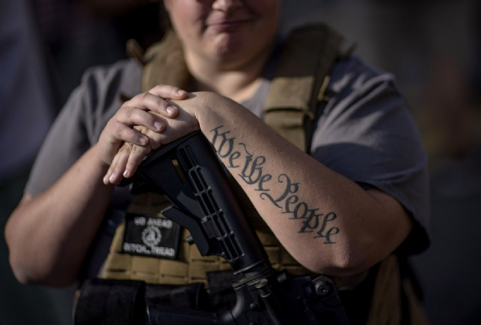 "The tattoo ""We The People"", a phrase from the US Constitution, decorates the arm of Trump supporter Michelle Gregoire as she rests her hand on her gun during a protest. Source: AP"