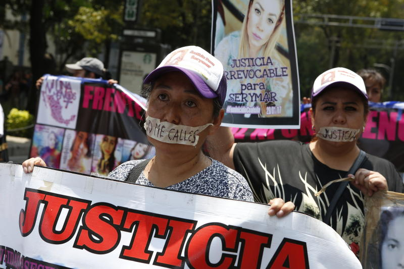 """Mothers tape their mouth with the messages """"Don't shut me up"""" and """"Justice"""" for their daughters during a silent march to remember murdered women and demand justice for them in Mexico City, Sunday, Sept. 8, 2019. Hundreds of women have taken to the streets of Mexico City to demand justice for loved ones, girls and countless women who have been sexually assaulted, murdered or gone missing in one of the most dangerous countries in the world to be a female. (AP Photo/Ginnette Riquelme)"""