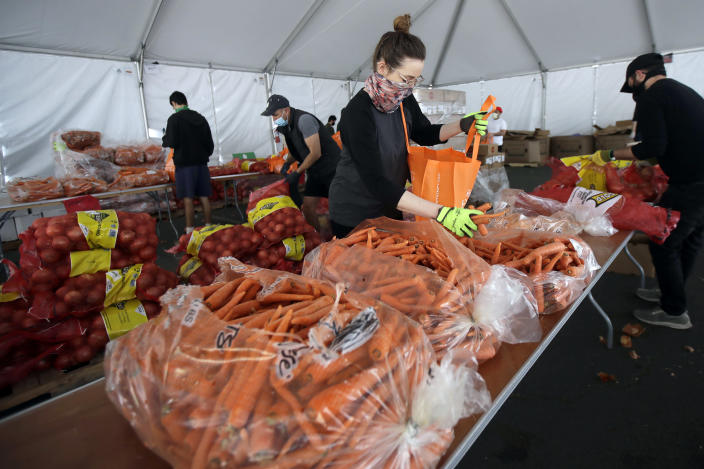 FILE - In this April 18, 2020, file photo, San Francisco-Marin Food Bank volunteers pack food into bags to be delivered to people in San Francisco. About 25 million Americans will be eligible for more food assistance money under a new policy adopted by President Joe Biden's administration under a change announced Thursday, April 1, 2021. (AP Photo/Jeff Chiu, File)