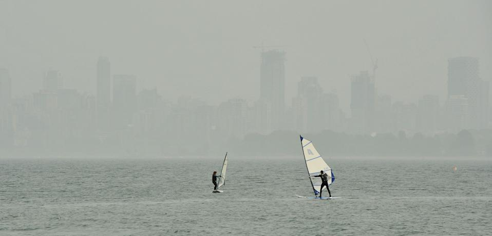 People windsurf in Burrard inlet as the heavy smog and smell of wood smoke hangs over the Vancouver, British Columbia skyline in the background on September, 16, 2020. - Smoke from California and Oregon wildfires has cloaked Vancouver, known for its majestic mountain views and fresh ocean breezes, in the dirtiest air in the world this week. Days have been spent smarting under a thick haze that has irritated eyes and throats, and sent asthmatics gasping for breath. It has also complicated Covid-19 testing. On September 18, 2020, despite forecasted smoke-clearing rain storms, the city, 800 miles (1,300 km) north of the biggest California fires, topped for the second time this week the World Air Quality Index for worst air quality, after briefly ceding first place to fire-stricken Portland, Oregon. (Photo by Don MacKinnon / AFP) (Photo by DON MACKINNON/AFP via Getty Images)
