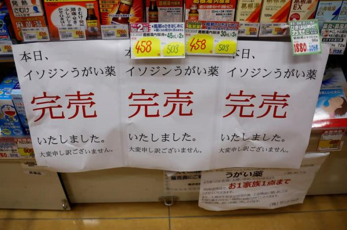 FILE PHOTO: Banners notifying sold-out of gargling medicine are displayed at empty shelves at a drugstore in Tokyo