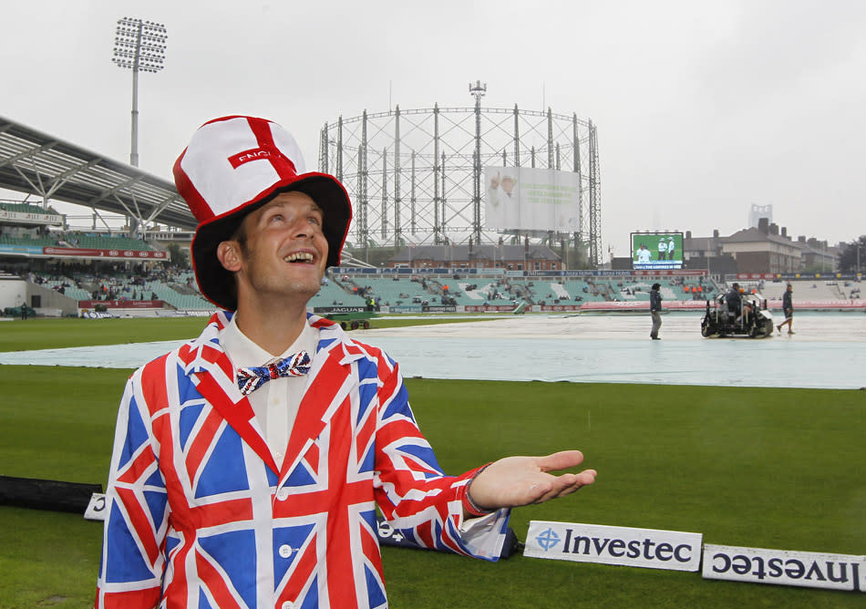 A spectator poses for a photograph after rain delays the start of the fourth day's play of the fifth Ashes cricket Test match between England and Australia at the Oval cricket ground in London on August 24, 2013. AFP PHOTO / IAN KINGTON