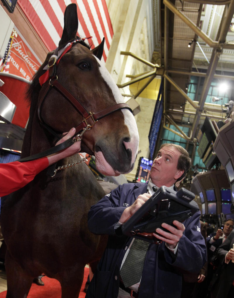 Trader Jonathan Niles encounters a Budweiser Clydesdale on the trading floor of the New York Stock Exchange, that was part of opening bell ceremonies  in observance of Major League Baseball's opening day, Thursday, March 31, 2011. (AP Photo/Richard Drew)