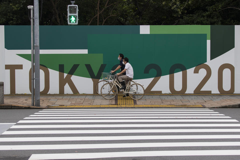 Men wearing face masks ride bicycles along the wall installed to close off a park being prepared for the Olympics and Paralympics Games in Tokyo on Thursday, July 1, 2021. (AP Photo/Hiro Komae)