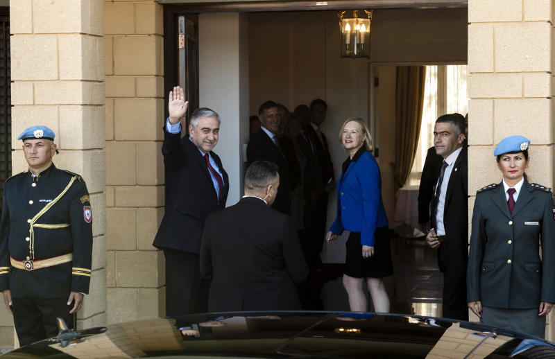 Turkish Cypriot leader Mustafa Akinci, waves to the media, with UN Secretary General's Special Representative to Cyprus Elizabeth Spehar, centre right, for their meeting with Cyprus President Nicos Anastasiades inside the UN buffer zone in divided capital Nicosia, Cyprus, Friday. Oct. 26, 2018. The rival leaders of ethnically divided Cyprus are meeting for the first time in six months to scope out the chances of resuming stalled reunification negotiations. (Iakovos Hatzistavrou/Pool via AP)