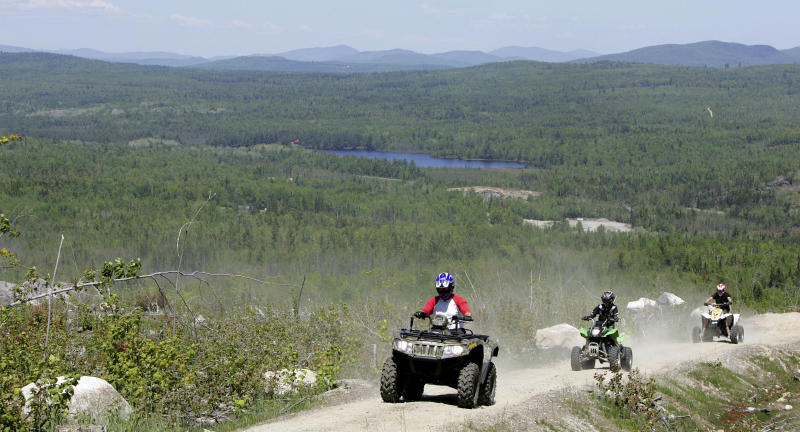 "FILE - In this Sunday, May 23, 2010 file photo, Jude Stohl leads Leigha Cicchetto, and his son Ethan Stohl on a ride through Jericho Park's trail system in Berlin, N.H. In New Hampshire, a new interconnected all-terrain vehicle trail system dubbed ""Ride the Wilds"" will officially open June 15, 2013 capping years of work by more than a dozen off-road vehicle clubs who worked with state agencies and local communities to link 1,000 miles of trails across Coos County. (AP Photo/Jim Cole, File)"