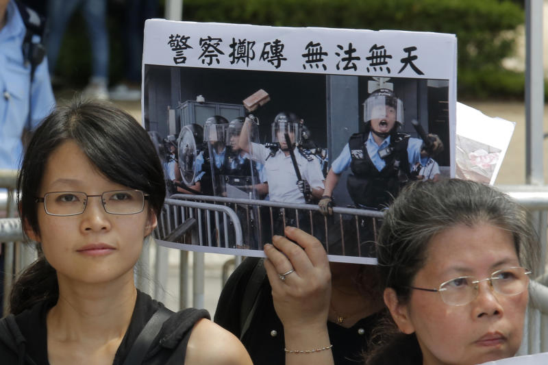 """Various of activist groups from parents and religious hold placards featuring a police throwing a brick with Chinese reading """"Police throwing brick is lawlessness"""" outside the government office demanding that stop shooting their kids in Hong Kong, Thursday, June 20, 2019. A Hong Kong student group demanded Wednesday that the city completely scrap a politically charged extradition bill and agree to investigate police tactics against protesters before a Thursday deadline or face further street demonstrations. (AP Photo/Kin Cheung)"""