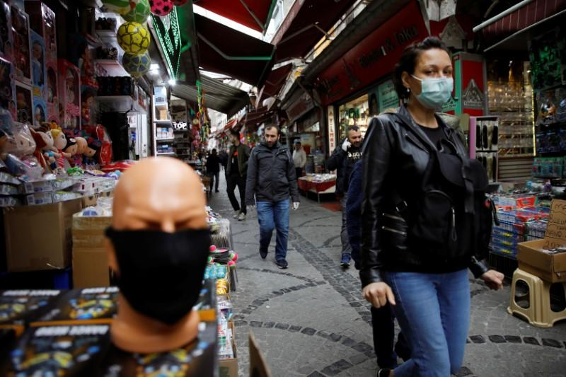 A woman wearing a protective face mask walks in a market at Eminonu neighbourhood during the outbreak of coronavirus disease (COVID-19), in Istanbul