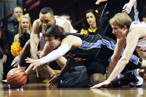 South Dakota State's Jordan Dykstra, center, dives after a loose ball with Minnesota's Joe Coleman, left and Elliot Eliason, right, during the first half of an NCAA college basketball game, Tuesday, Dec. 4, 2012, in Minneapolis. (AP Photo/Tom Olmscheid)