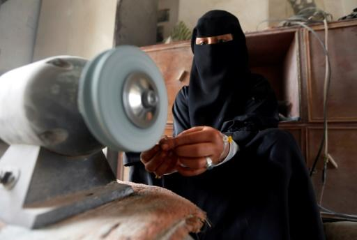 Safaa al-Faqih, one of the few female Yemeni craftsmen working in the precious stones industry in Yemen, crafts a stone in the old city of the capital, Sanaa