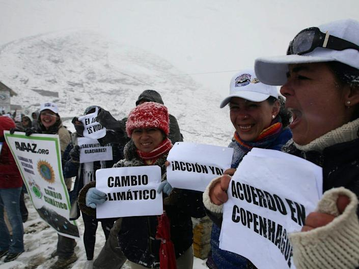 """Protesters hold signs that read in Spanish """"Climate Change,"""" """"Action Now!,"""" and """"Remember Copenhagen"""" as they demonstrate on Glacier Chacaltaya in the Andes mountains in 2009."""