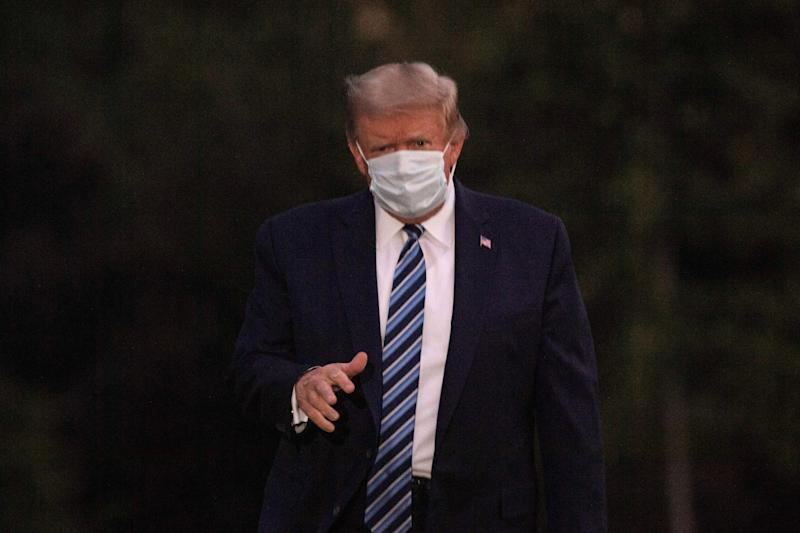 US President Donald Trump gestures to the press as he arrives at the White House wearing a facemask upon his return from Walter Reed Medical Center, where he underwent treatment for Covid-19, in Washington, DC, on October 5, 2020. (Photo by NICHOLAS KAMM / AFP) (Photo by NICHOLAS KAMM/AFP via Getty Images)