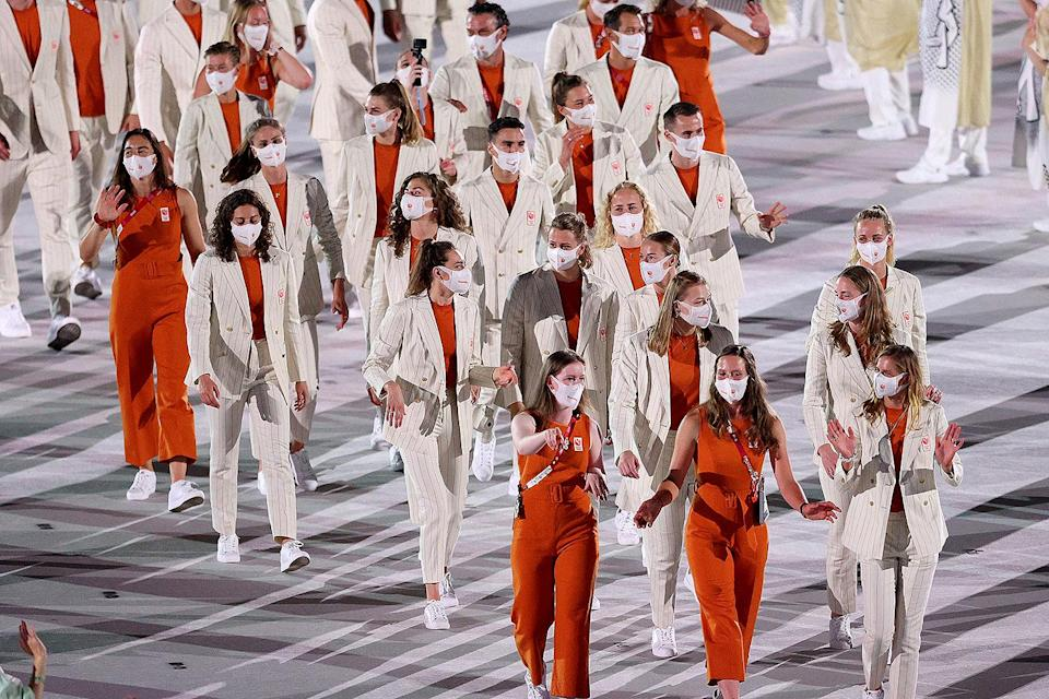 <p>Are the delegates from Netherlands heading to the opening ceremony or to the office? Some delegates wore belted burnt orange (the national color) and cream sleeveless jumpsuits, while others wore pinstripe suits. </p>