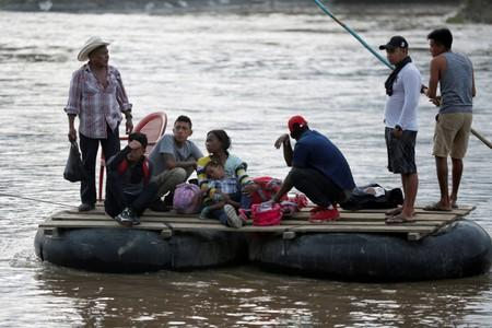 Migrants and locals cross the Suchiate river on a raft from Tecun Uman, in Guatemala, to Ciudad Hidalgo, as seen from Ciudad Hidalgo