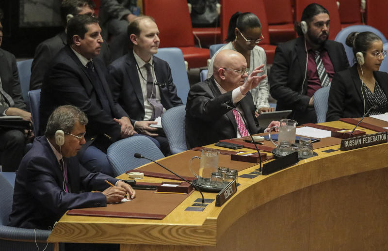 Russia's United Nations Ambassador Vasily Nebenzya, seated front center, raise his hand signaling he would abstain from a vote in the U.N. Security Council for Yemen related sanctions, Tuesday, Feb. 25, 2020, at U.N. headquarters. The Security Council voted to approve a revised British draft resolution extending targeted sanctions in Yemen. (AP Photo/Bebeto Matthews)
