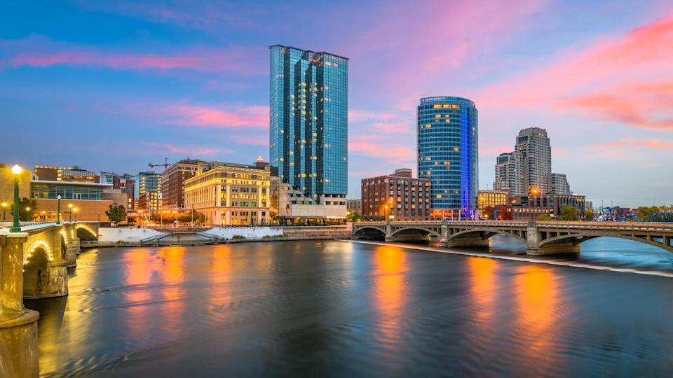 Grand Rapids, Michigan, USA downtown skyline on the Grand River at dusk.