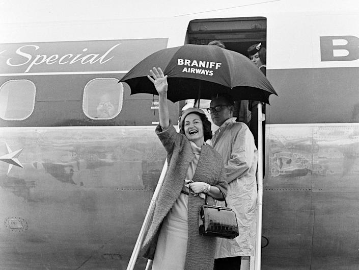 """Lady Bird Johnson, wife of President Lyndon Johnson, greets well wishers upon landing aboard a Braniff International Airways Lockheed Electra dubbed """"The Lady Bird Special"""""""
