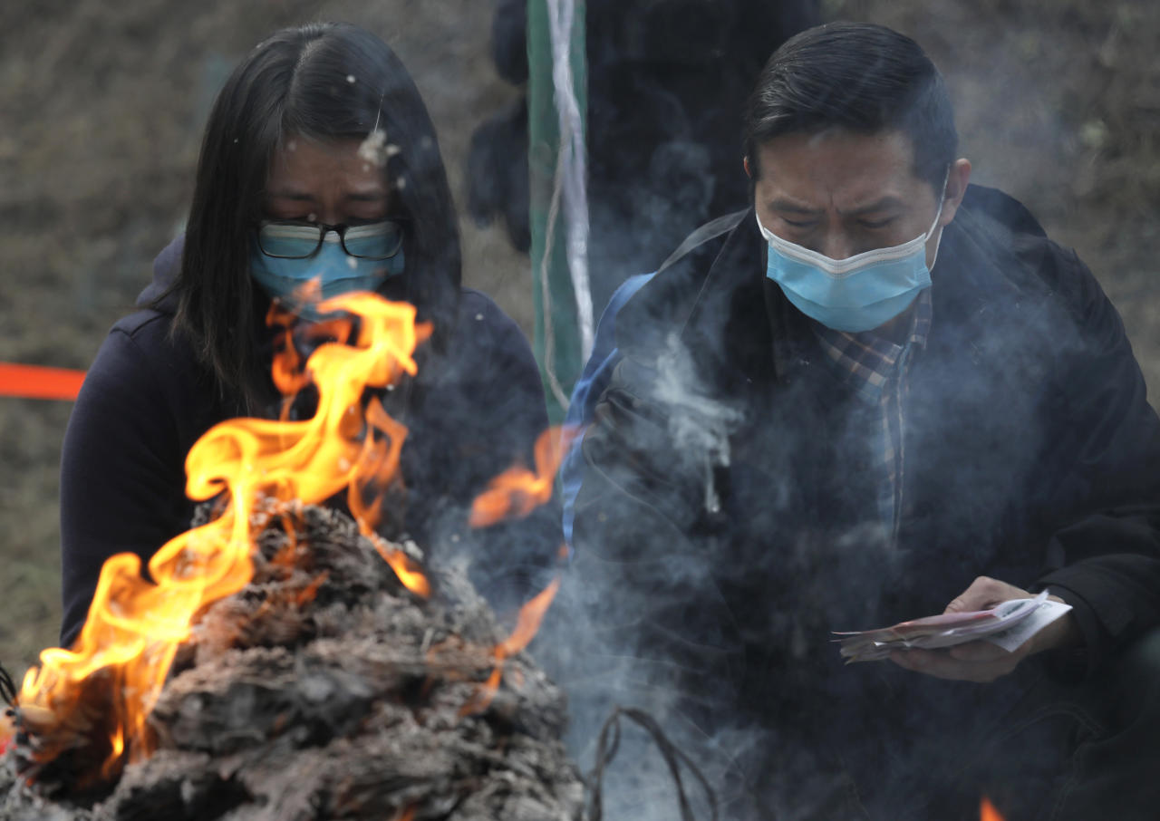 <p>Relatives burn paper money as they pay last tributes to bus crash victims in Hong Kong, Feb. 11, 2018. (Photo: Vincent Yu/AP) </p>