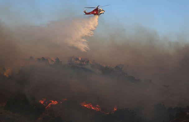 PHOTO: A firefighting helicopter works the Saddleridge Fire on Oct. 11, 2019, near Porter Ranch, Calif. (Mario Tama/Getty Images)