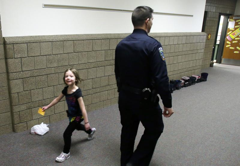 In a photo made Thursday, Feb. 21, 2013, a young girl, smiles as she passes police officer Jeff Strack as he walks the hallway of Jordan Elementary School in Jordan, Minn. In what is believed to be the first of its kind nationwide, the small city south of Minneapolis is taking school security to a new level by setting up satellite offices inside the public school buildings. (AP Photo/Jim Mone)