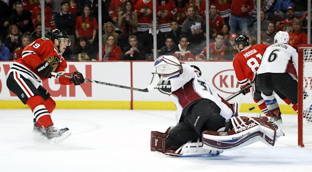 Chicago Blackhawks center Jonathan Toews (19) shoots and scores past Colorado Avalanche goalie Jean-Sebastien Giguere during the second period of an NHL hockey game Friday, Dec. 27, 2013, in Chicago. (AP Photo/Charles Rex Arbogast)