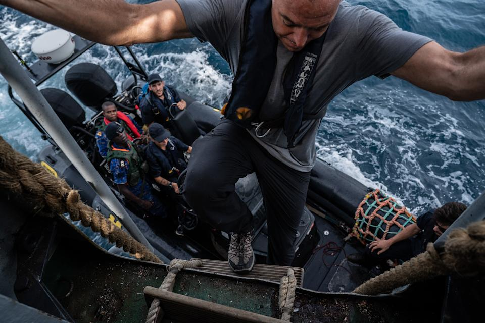 Ian climbs down into Sea Shepherd speedboat filled with Gambian Navy and fisheries officers. (Fábio Nascimento / The Outlaw Ocean Project)
