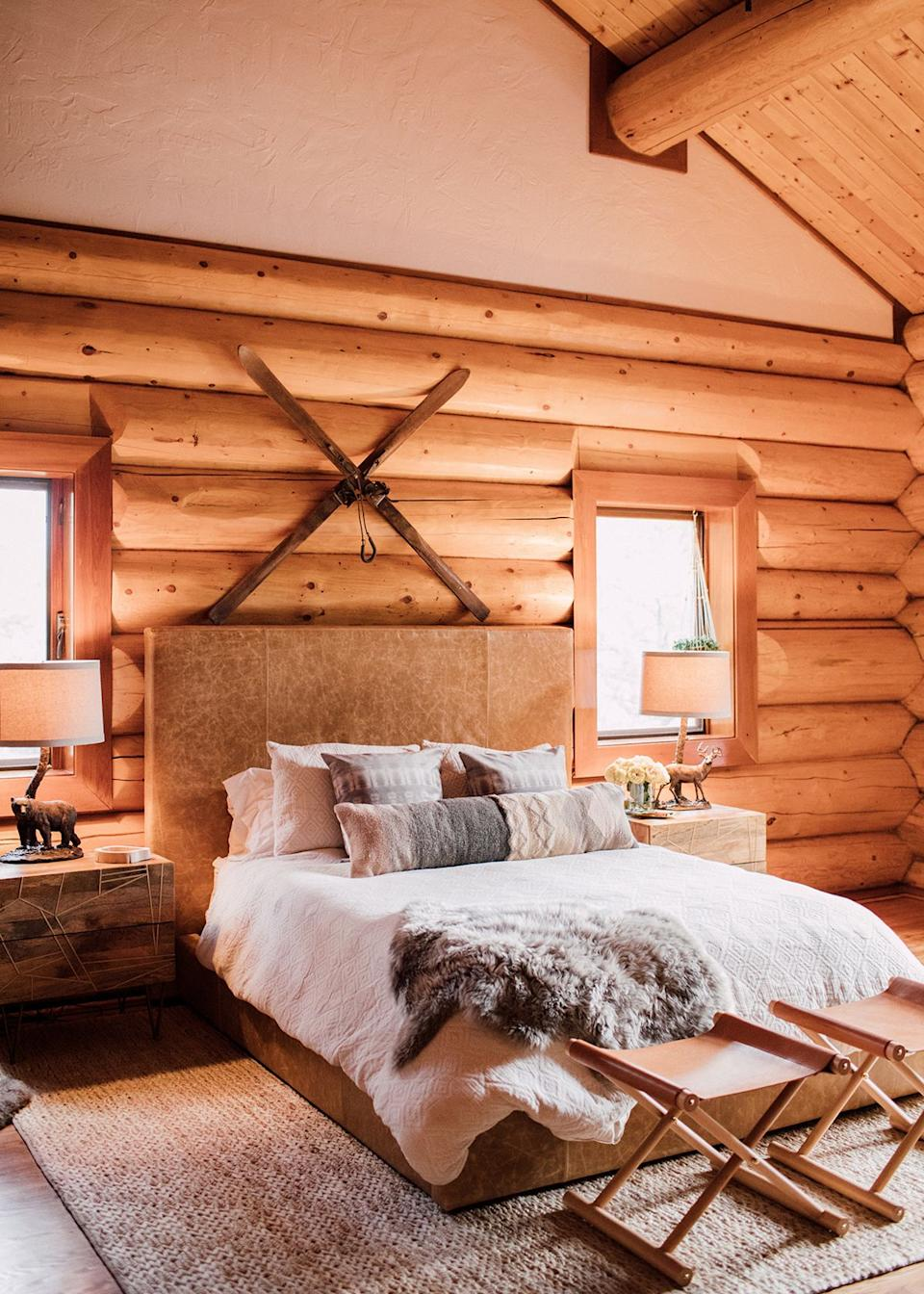 In the bedroom, cozy vibes abound. A fur throw, soft lighting, and plenty of pillows make you want to curl up and read a great book in this plush retreat.