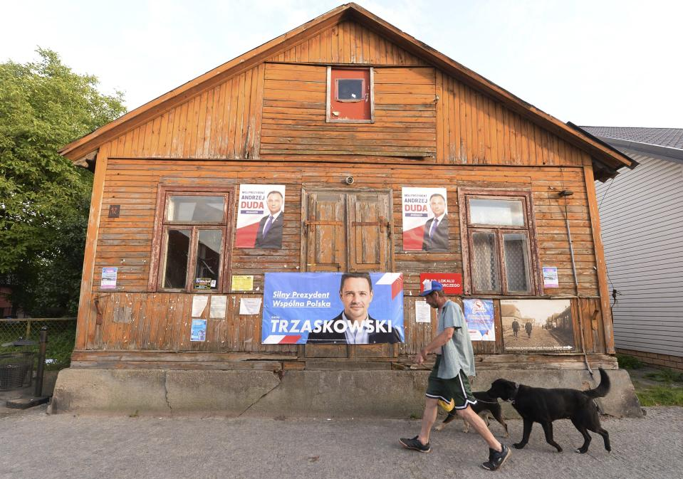 A man walks his dogs outside a home with campaign posters showing two candidates in Poland's weekend presidential election, Polish President Andrzej Duda and his challenger, Warsaw Mayor Rafal Trzaskowski, in Tykocin, Poland, on Tuesday July 7, 2020. Two bitter rivals are heading into a razor's-edge presidential runoff election Sunday in Poland that is seen as an important test of populism in Europe after a campaign that exacerbated a conservative-liberal divide in the country. (AP Photo/Czarek Sokolowski)