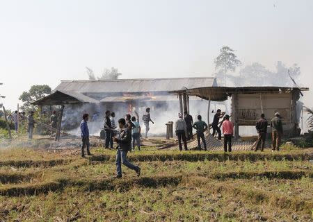 Tribal plantation workers burn houses belonging to indigenous Bodo tribesmen after ethnic clashes in Balijuri village, in Sonitpur district in the northeastern Indian state of Assam on December 24, 2014. REUTERS/Stringer