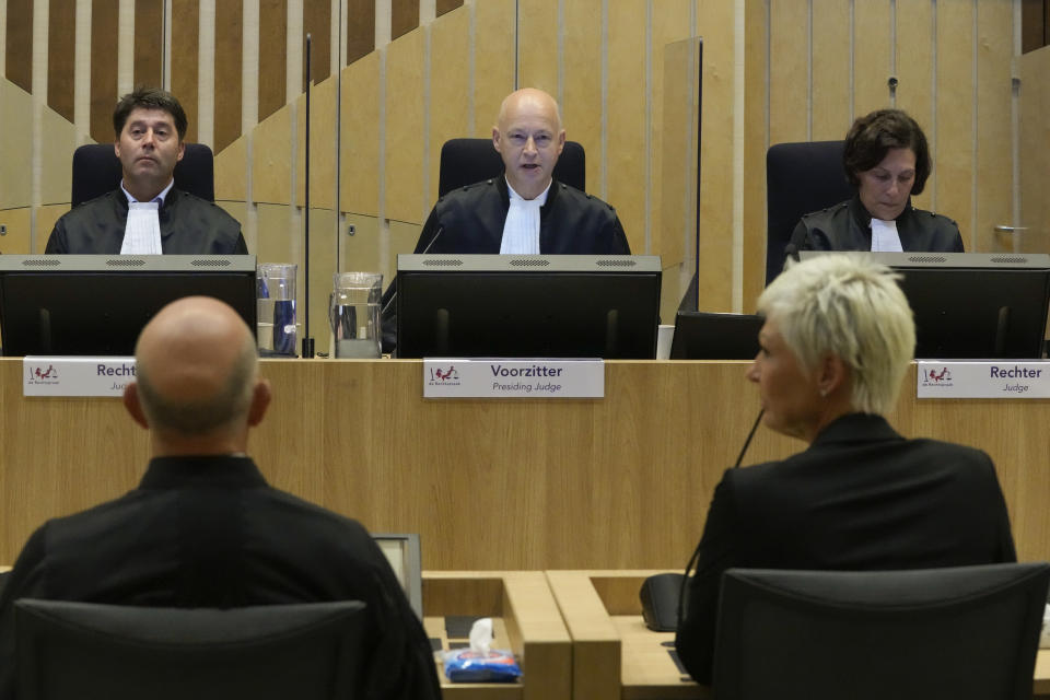 Presiding judge Hendrik Steenhuis, center, waits for Ria van der Steen, who lost her father and stepmother in the MH17 crash, front right, to give testimony in court in the trial of four men charged with murder over the downing of Malaysia Airlines flight MH17, at Schiphol airport, near Amsterdam, Netherlands, Monday Sept. 6, 2021. Relatives of some of the 298 people killed in the downing of Malaysia Airlines flight MH17 tell a Dutch court about the impact on their lives of the disaster during the trial of three Russians and a Ukrainian charged with involvement in bringing down the Amsterdam-Kuala Lumpur flight more than seven years ago. (AP Photo/Peter Dejong)