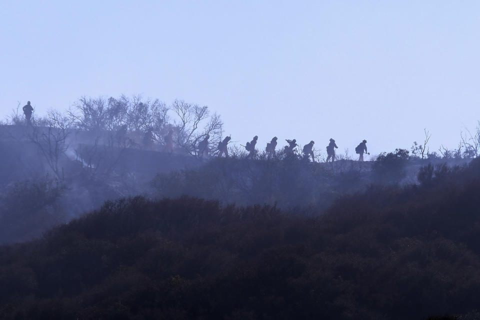 A hotshot hand crew walks in line during a wildfire in Topanga, west of Los Angeles, Monday, July 19, 2021. A brush fire scorched about 15 acres in Topanga today, initially threatening some structures before fire crews got the upper hand on the blaze, but one firefighter suffered an unspecified minor injury. (AP Photo/Ringo H.W. Chiu)