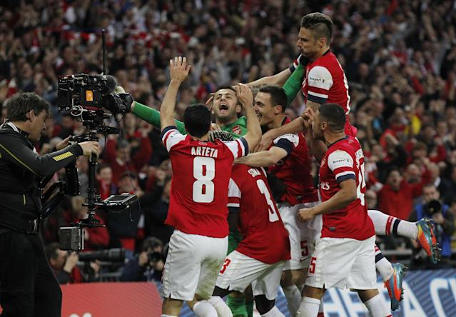 Arsenal players celebrate their win against Wigan Athletic at the end of their English FA Cup semifinal soccer match at Wembley Stadium in London, Saturday, April 12, 2014. (AP Photo/Sang Tan)
